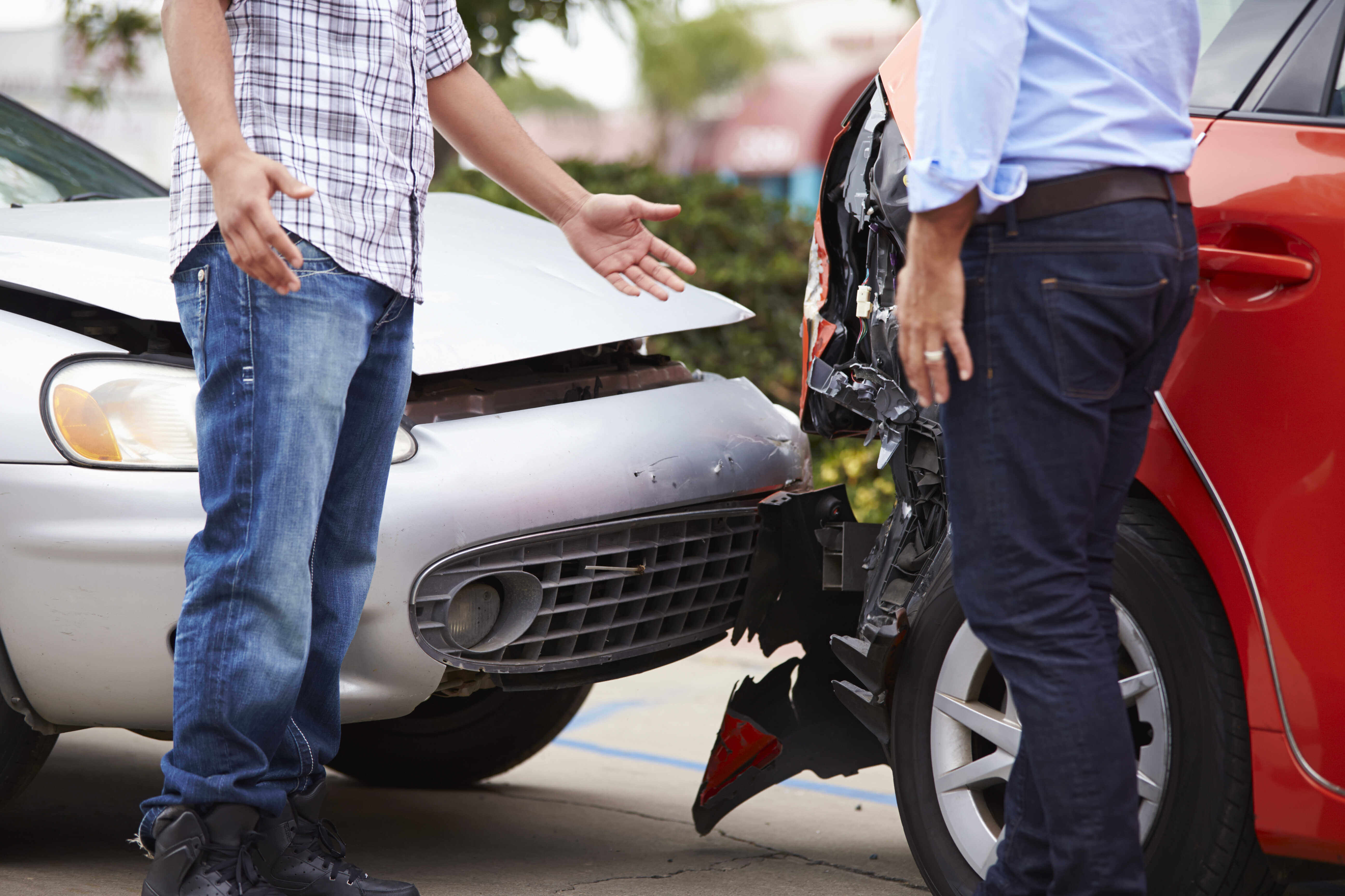 two men talking beside car wreck