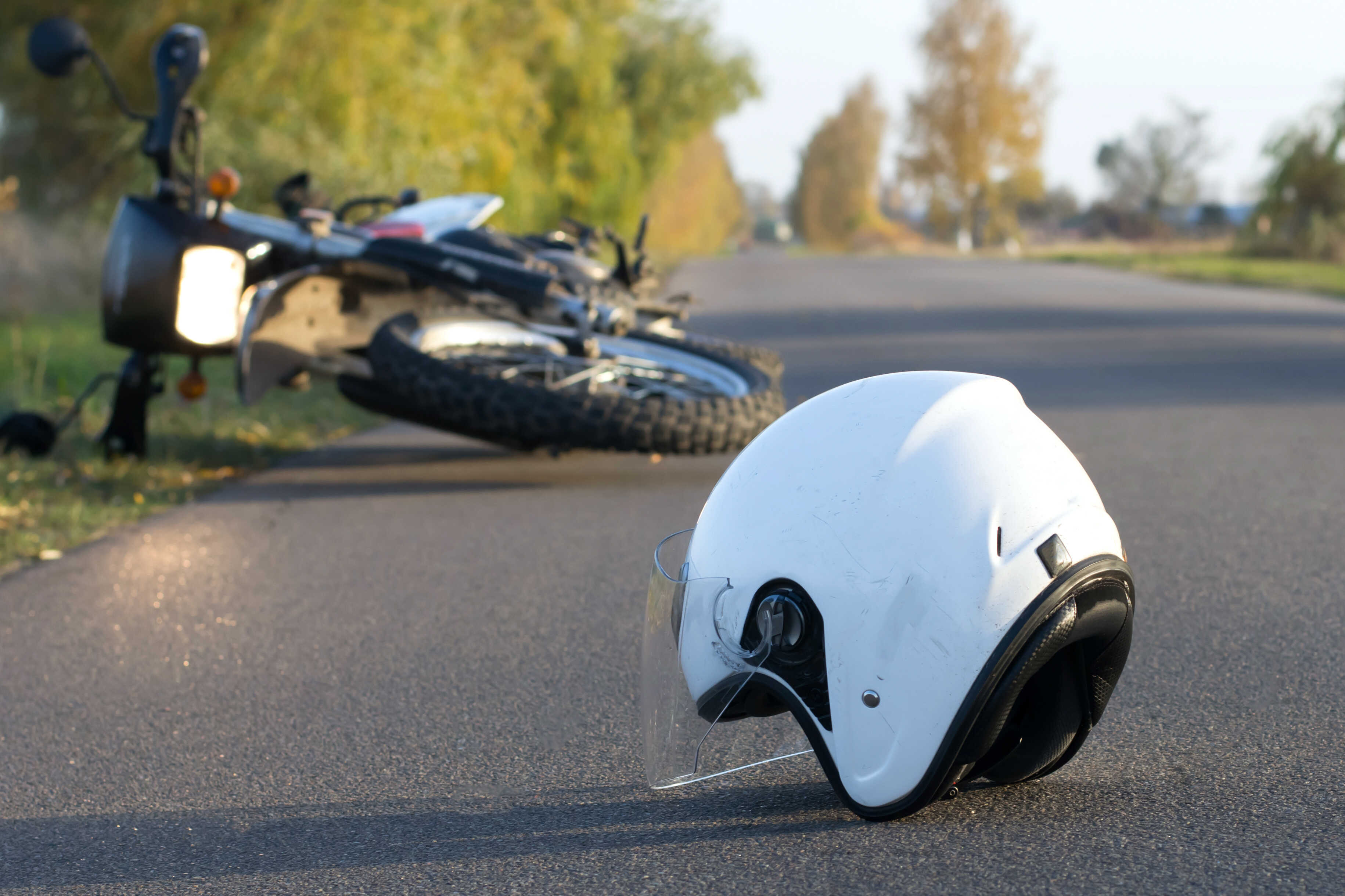 white helmet on pavement beside overturned motorcycle